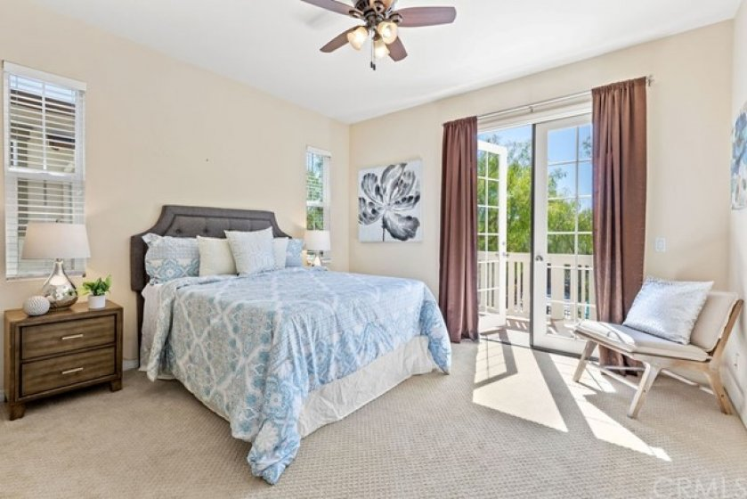 The spacious primary bedroom is located on the second level and features french doors leading to a private balcony.