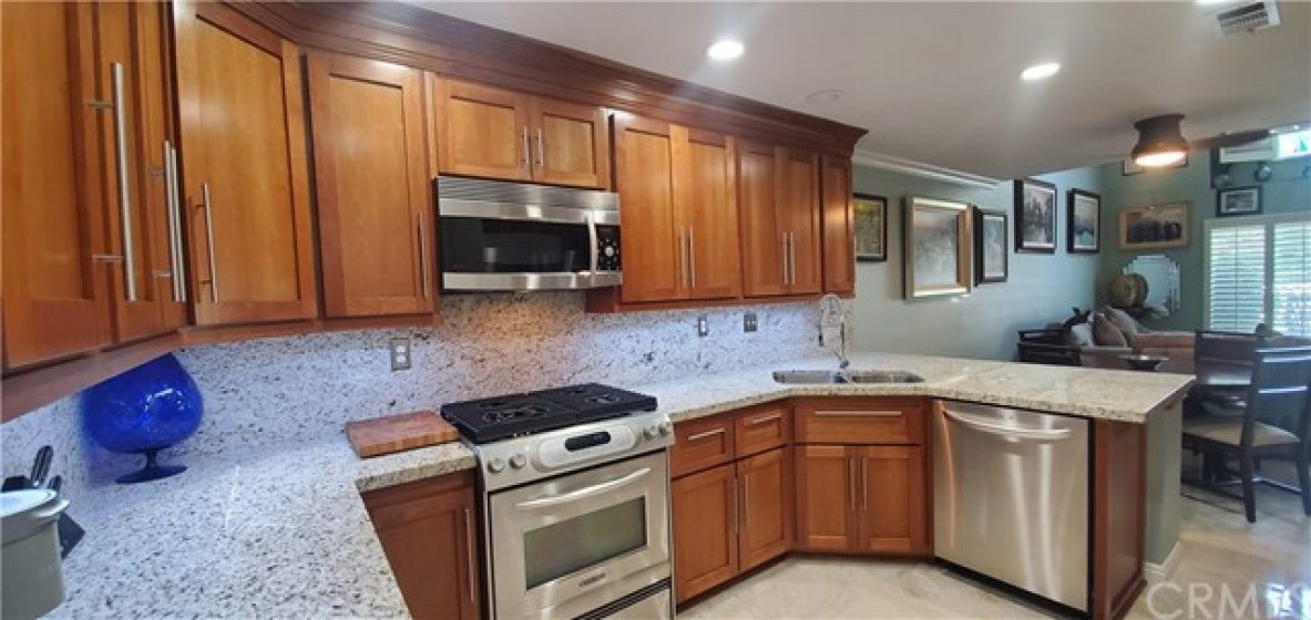 Cherry Wood Cabinets with polished Nickel hardware - dove tail soft close with full extension drawers Stainless Steel appliances ( Fridge doesn't convey)