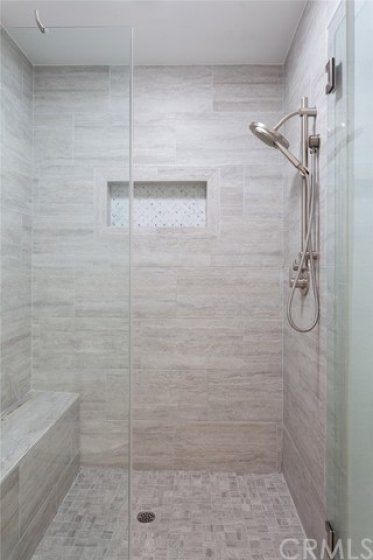 Remodeled master bath features an oversized step-in shower with glass enclosure & built-in bench seat.