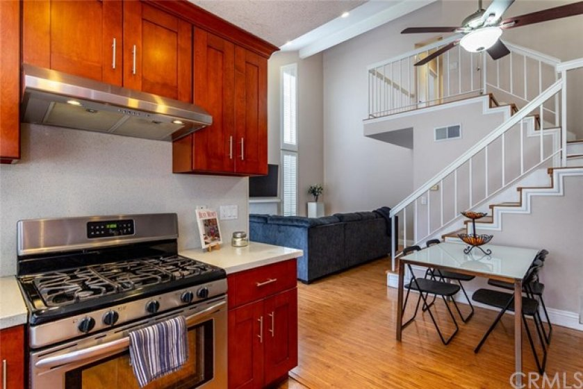 5 Burner gas range oven in the kitchen and an open view to the living room.