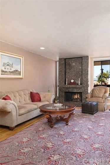 The fireplace in the living room is faced with beautiful granite tile
