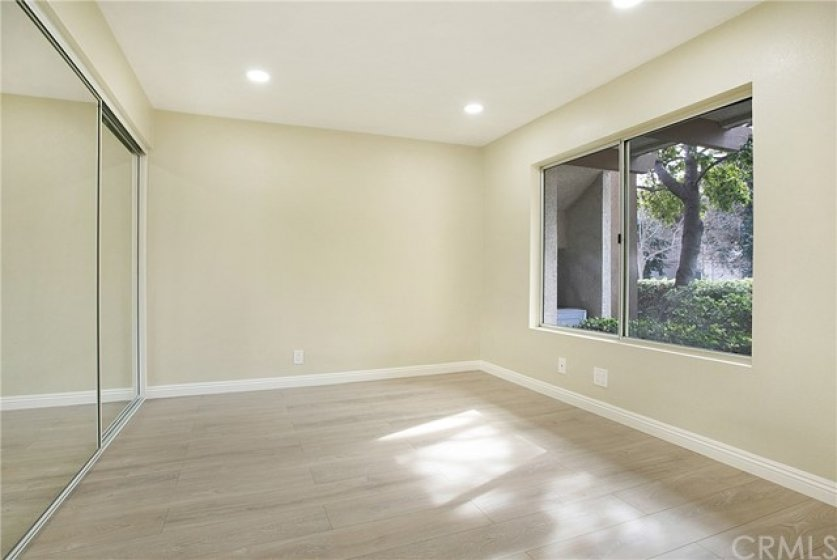 Large secondary bedroom with new laminate floors and mirrored closet doors.