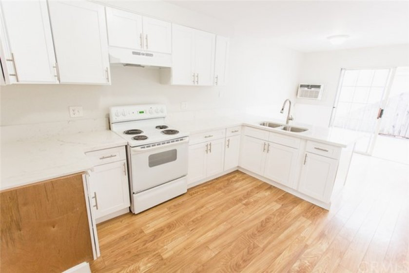 Remodeled kitchen with new cabinets and quartz counters.