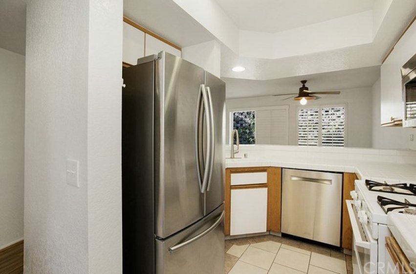 Newer stainless steel dishwasher and refrigerator compliment your bright kitchen.