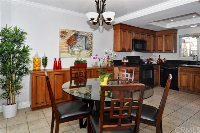 Spacious Dining Room with Custom-Built Buffet Bar & Cabinetry is Open to Remodeled Granite Kitchen