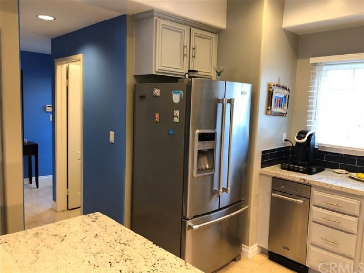 Kitchen located near the guest bathroom & entry way