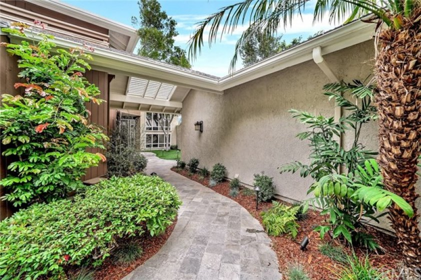 The elegant courtyard entry is verdant with plants and offers serene privacy to the home.