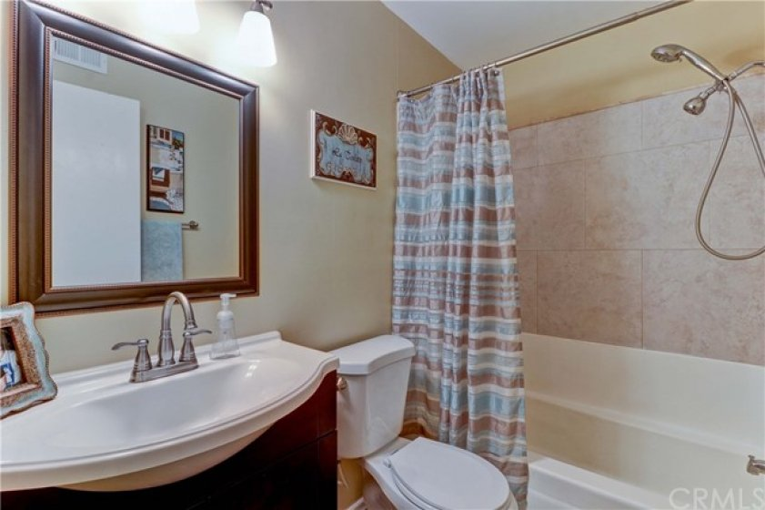 Sleek vanity and updated tub/shower surround plus dual shower head in the upstairs hall bathroom.