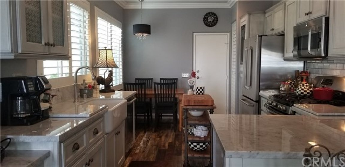 Plantation shutters, stainless steel GE Cafe line appliances, Carerra marble counters and subway tile, custom cabinets, glass front as well, wine rack, country sink, direct access garage, crown moulding, stuffing wood floor