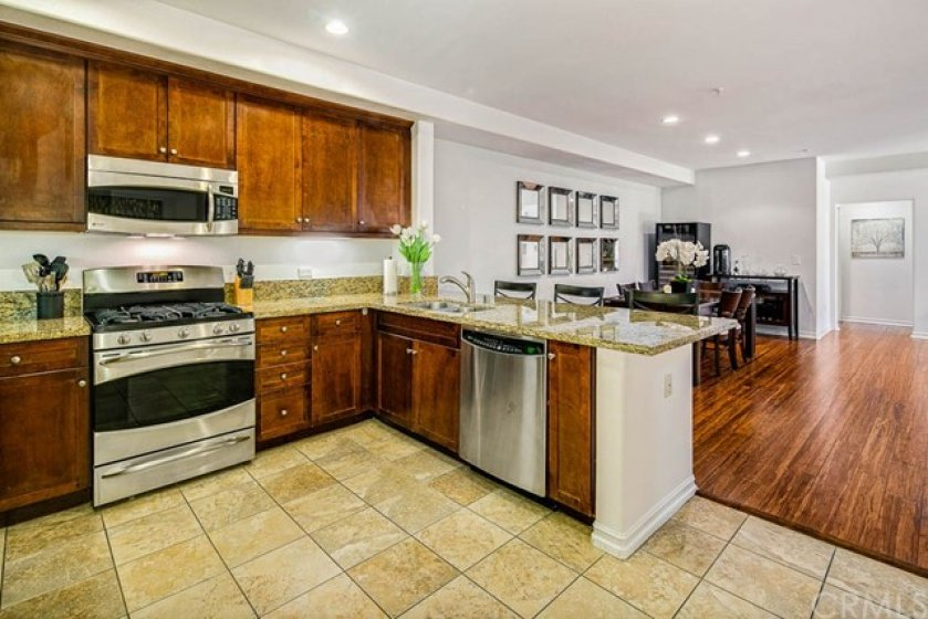 Kitchen boasts high-end stainless steel appliances, granite countertops, eat-on counter, and is open to the dining and living areas.  New paint, recessed lighting, wood flooring, and whole house surround sound system!