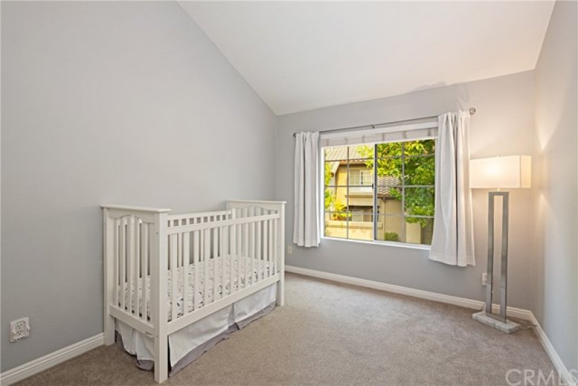 Upstairs secondary bedroom with vaulted ceilings and large windows