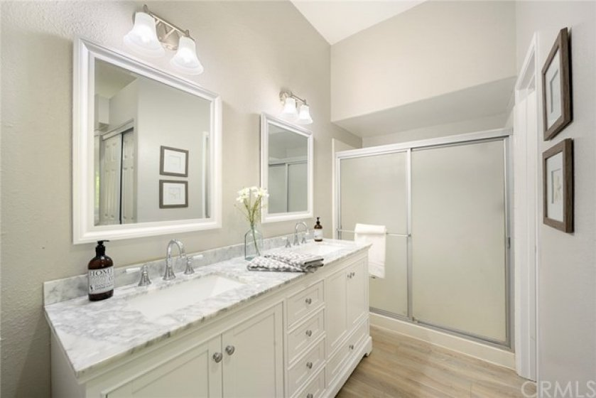 Master Bathroom with NEW white vanity with dual sinks and Carrera Marble Countertops, NEW mirrors, NEW light fixtures, walk-in shower, and tall ceilings!