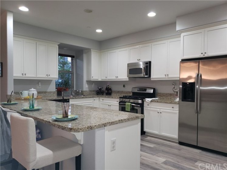 Isn't this lovely?  Loads of cabinet space - pantry out of view - refrigerator comes with the home as well.  Luxury Vinyl Plank (LVP) is waterproof, is throughout the first floor - is beautiful and easy to clean.  Dual pane windows, recessed lighting - open to living room to include everyone!