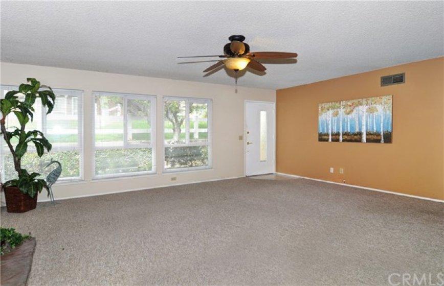 Living room view looking towards front door, lots of windows.