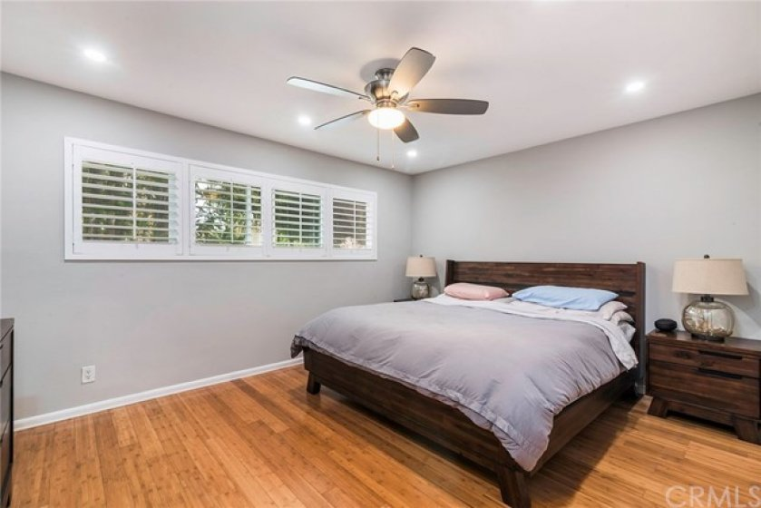 bedroom with newer plantation shutter and bamboo flooring