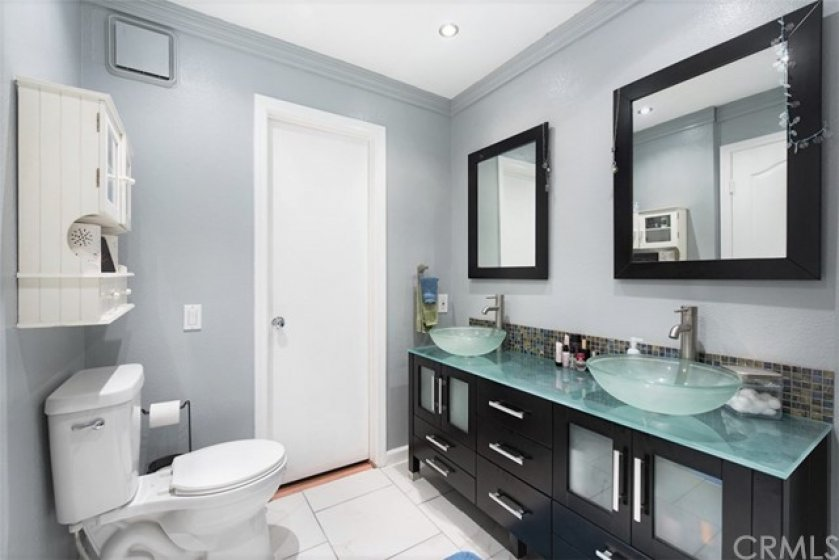 Designer master bathroom with dual sinks and entrance to walk in closet