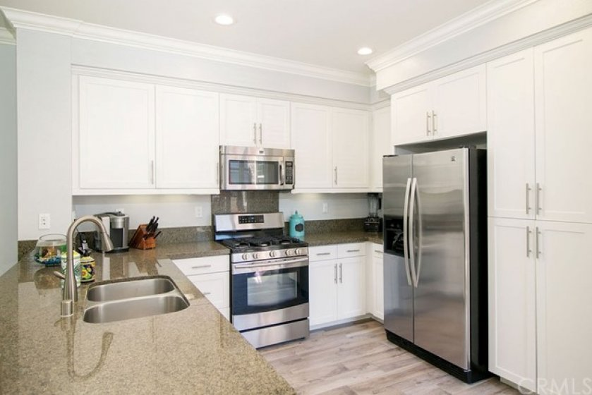 Granite counters, white cabinets and stainless steel appliances.