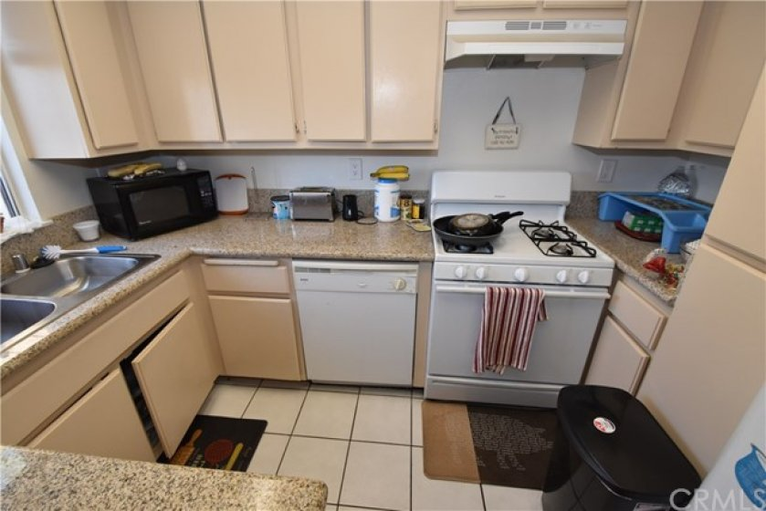 Spacious kitchen has granite counters, tile floors, dishwasher and dual stainless steel sink.