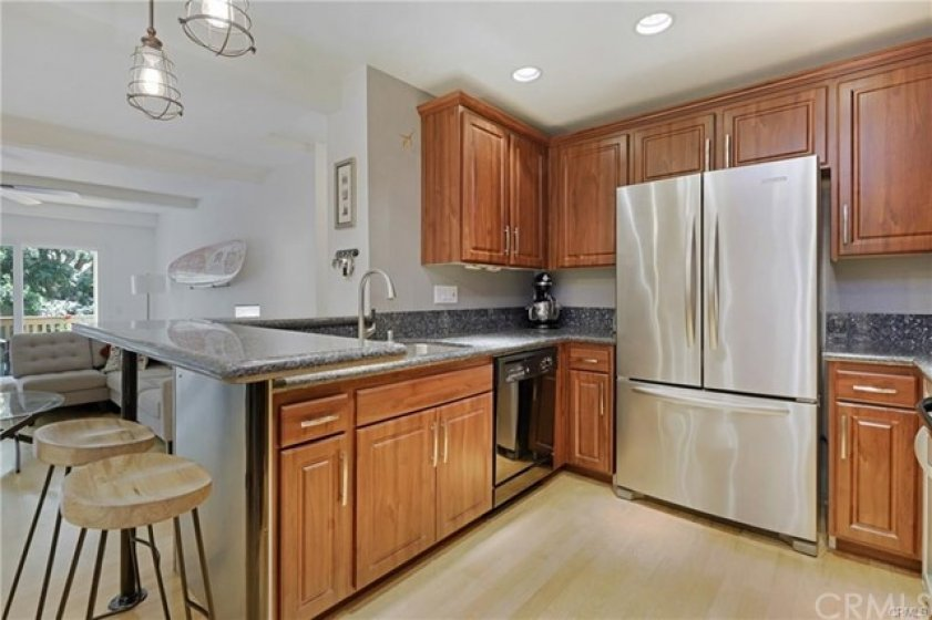 Beautiful kitchen cabinetry with sleek silver hardware, granite countertops, and backsplash. Stainless steel side by side refrigerator with freezer drawer below. Stainless double bowl sink.