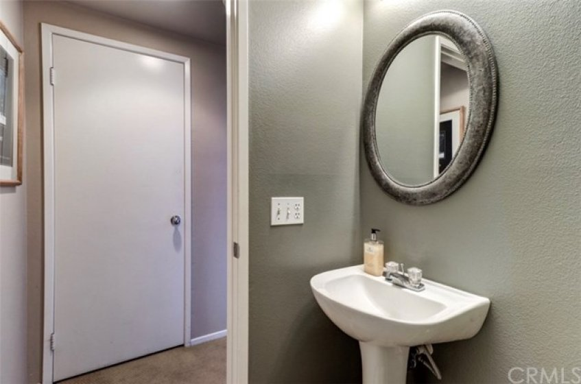 Downstairs powder room for your guests!  Easy access to this bathroom yet discretely tucked into a small hallway across from guest closet.  So smart!