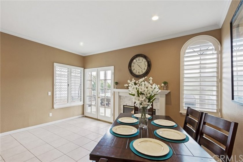 This space is upgraded with recessed lighting, crown mouldings and plantation shutters