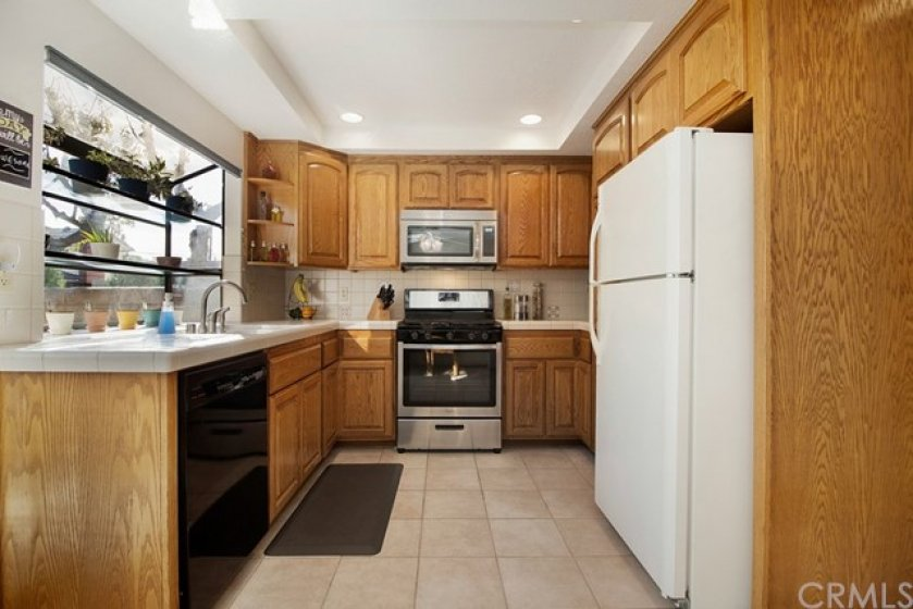 Remodeled kitchen with ample oak cabinetry; newer stainless stove & microwave + dishwasher, double sink & recessed lighting.
