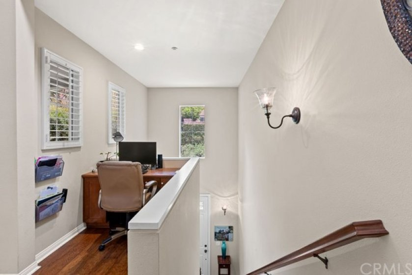 Office space on the main floor level at the top of the stairs looking out to the outdoors and natural light.