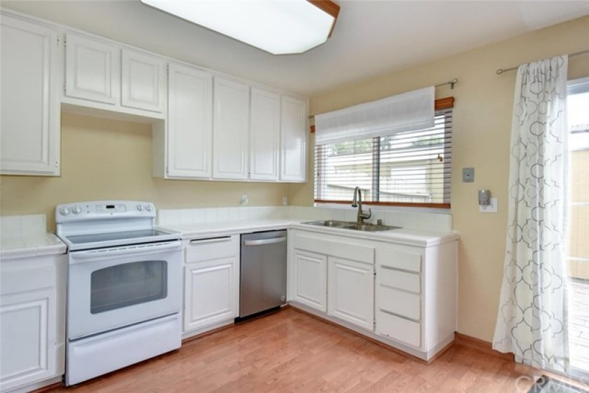 Bright kitchen with new stainless steel sink, garbage disposal and newer dishwasher.