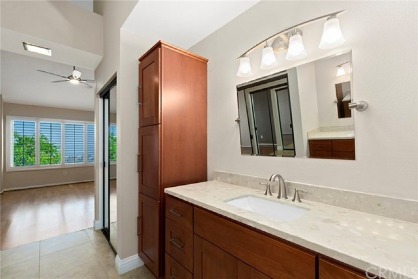 Upgraded and Beautifully Remodeled Master Bath with Granite Counter, Custom Vanities, Extra Storage, and Oversized Tiled Shower with Glass Enclosure