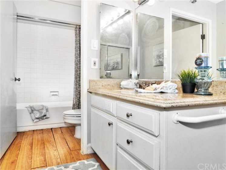 Bathroom has Granite Countertop, Tub/Shower Combo with Tile Surround, Bamboo Flooring, Dressing Area and Mirrored Closet