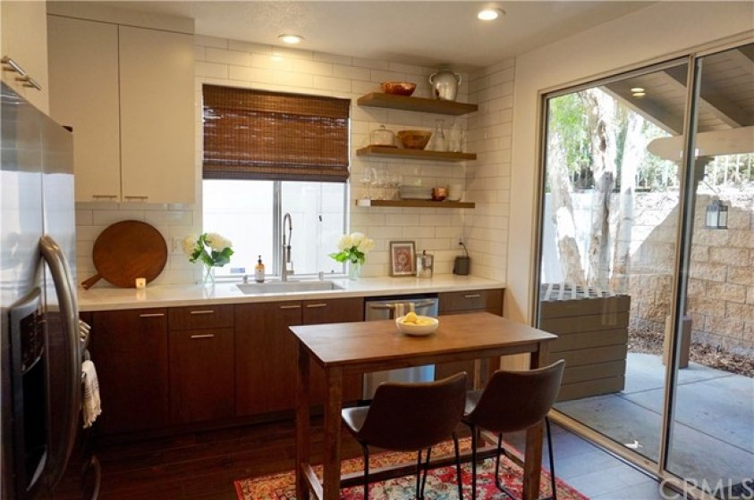 Redone kitchen with floating shelves for storing your goodies!  Kitchen island is perfect for breakfast for two!
