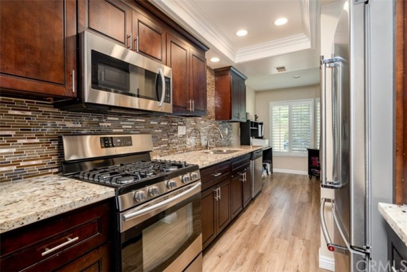 Upgraded kitchen with granite counters and stainless steel appliances.