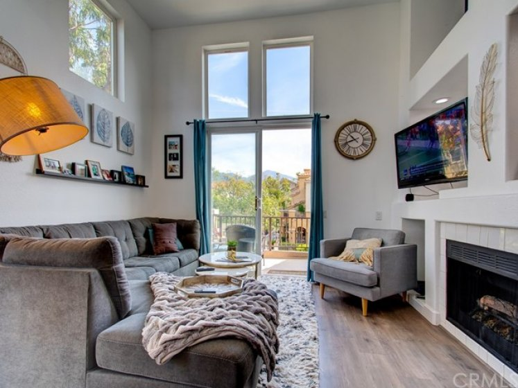 Bright living room with high ceiling, fireplace and view of Saddleback Mountain