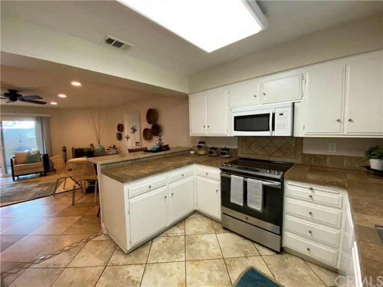 Kitchen overlooks breakfast bar, dining/living area and spacious patio.