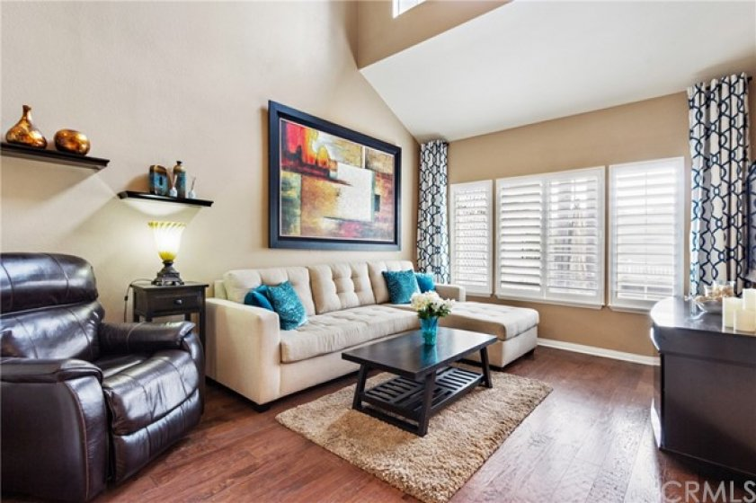 Dramatic high ceilings and beautoful wood flooring complement the open, bright living areas. Upgrades include custom plantation wood shutters