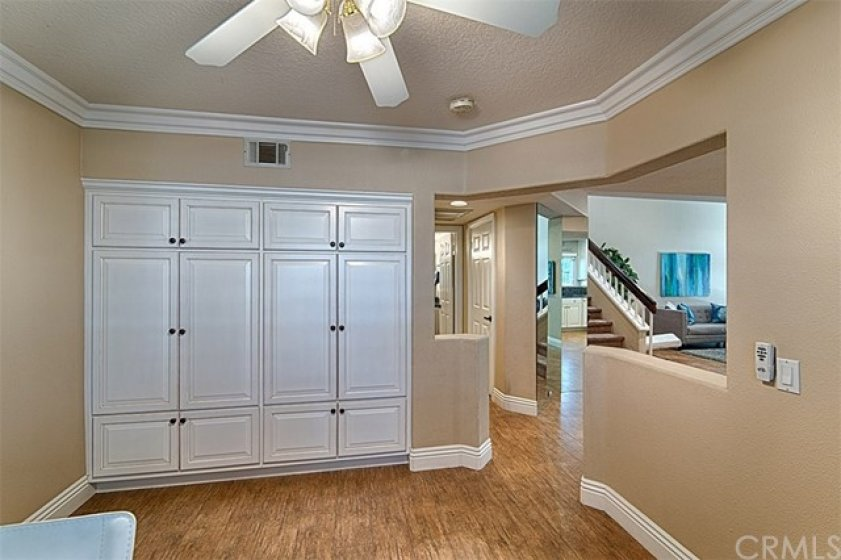 Downstairs bedroom, currently used as an office, has beautiful custom built in cabinets, large white crown molding and baseboards and a lighted ceiling fan.