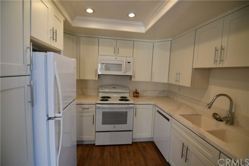 Completely remodeled kitchen. New soft close white cabinetry, quartz counter tops, new sink, new faucet, new upgraded range/oven, new microwave, new dishwasher, new laminate flooring, crown molding & recessed lighting.