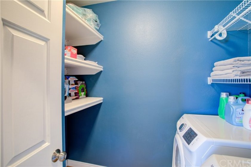 Laundry room features plenty of storage space.