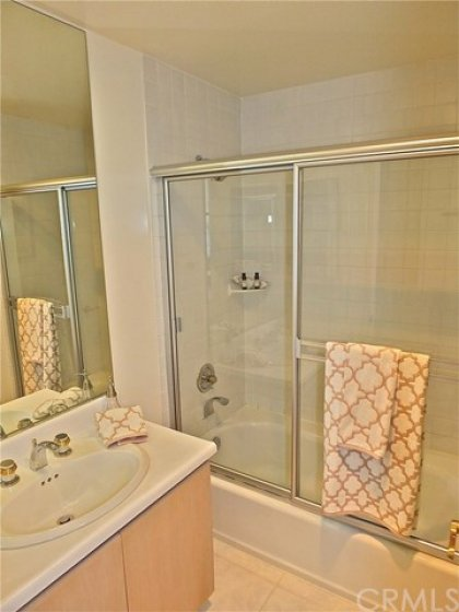 Hall bathroom that has a tub/shower combo and tiling that goes up to the ceiling.