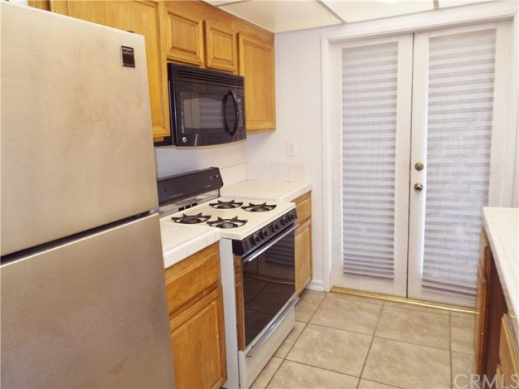 Kitchen with tile floors, gas range, microwave and tile counters.