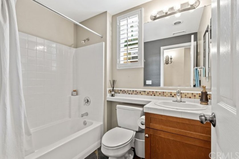 Main floor full bath with window for natural light conveniently located next to bedroom.