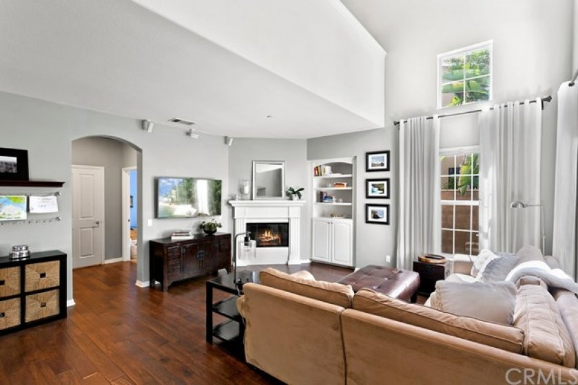Inside, stunning wood floors and a two story ceiling in the great room with fireplace, built-in, blinds and drapes.
