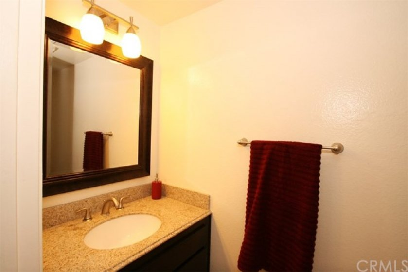 upgraded downstairs half bath with granite top, new mirror, faucet and light fixture