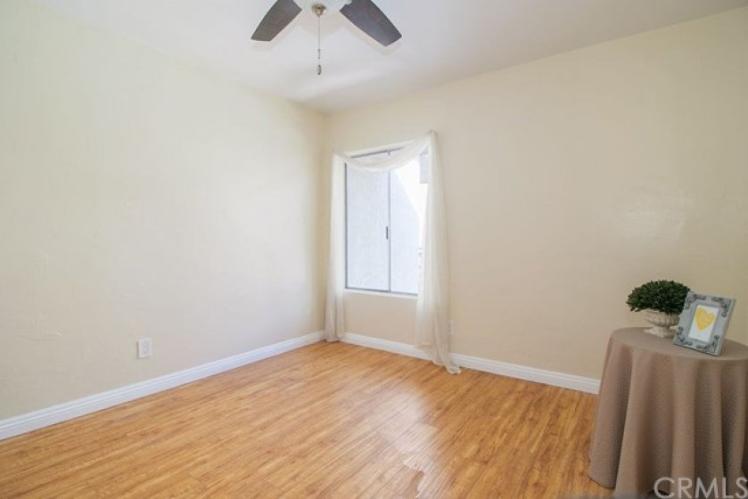 From this picture you see the ceiling fan, window, wood laminate flooring and base molding located throughout the home.