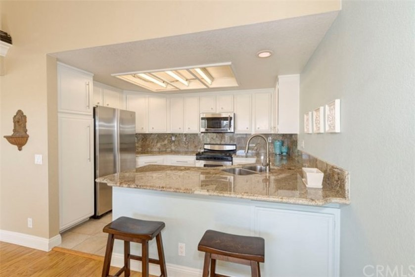 Granite Counter Tops and Stainless Steel appliances. Breakfast Bar and open to Dining Room with views out Sliding Glass Doors
