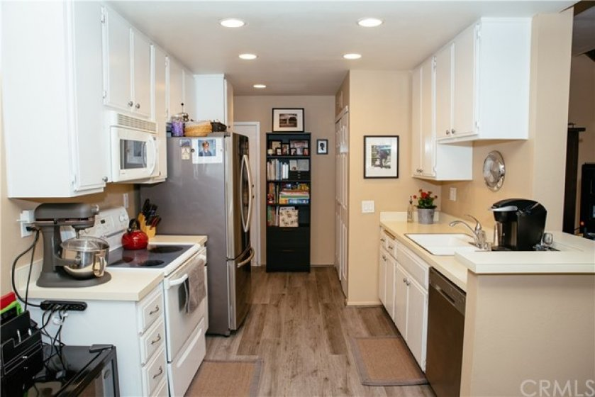 Kitchen with recessed lights, SS dishwasher, microwave, oven and stovetop plus laundry closet to the back right and easy access to one car attached garage.