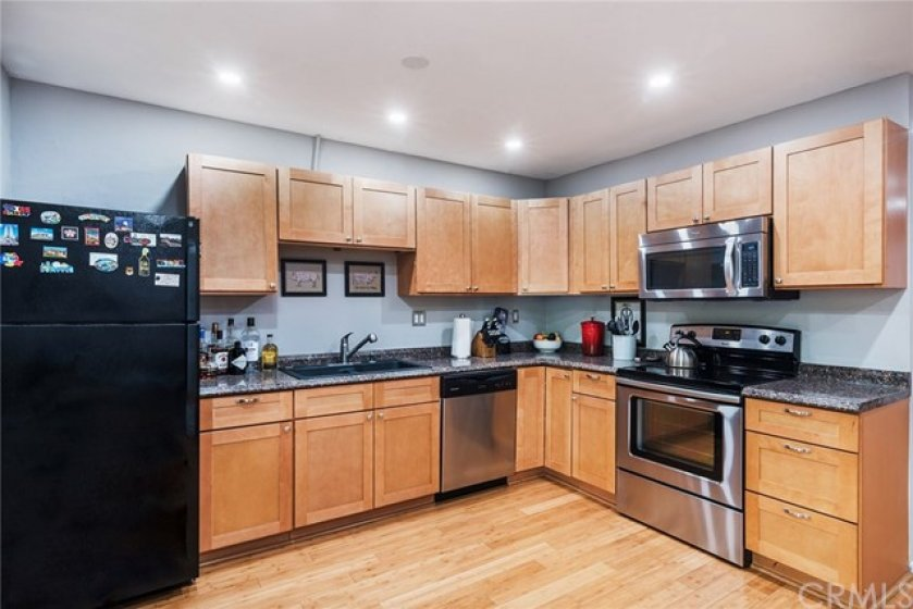 Updated kitchen with maple look cabinets and black and stainless steel appliances