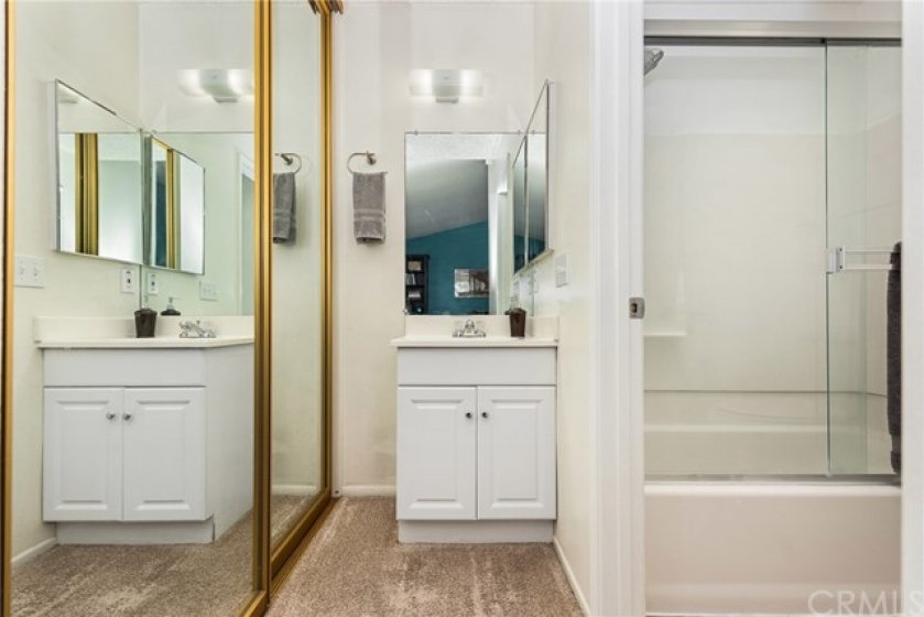Master bath with mirrored closet doors and enclosed shower/tub.