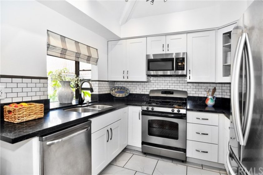 Remodeled kitchen with white shaker cabinets, stainless steel appliances, track lighting and garden window