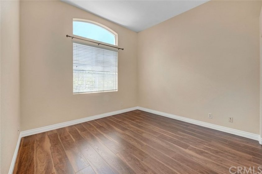 Spacious guest bedroom wth vaulted ceiling and wood laminate flooring